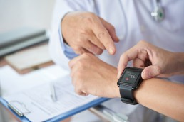 doctor using healthcare wearables to optimize treatment